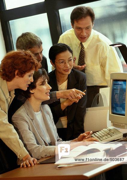 Fünf Geschäftsleute schauen auf den Computerbildschirm