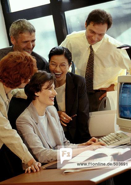 Fünf Geschäftsleute versammelten sich am Schreibtisch und lächelten.