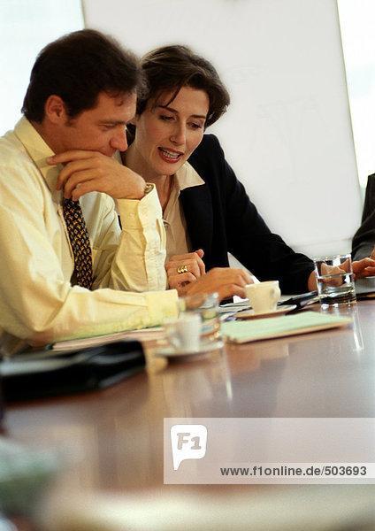 Geschäftsmann und Geschäftsfrau am Tisch sitzend