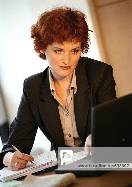 Geschäftsfrau beim Betrachten des Laptops und Schreiben