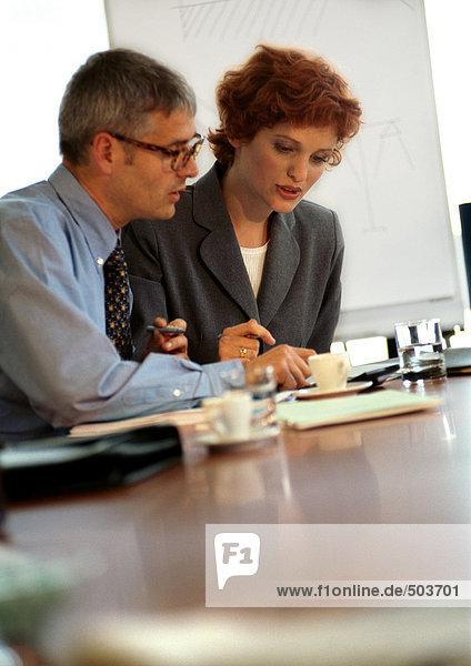 Geschäftsmann und Geschäftsfrau sitzen am Tisch und schauen nach unten.