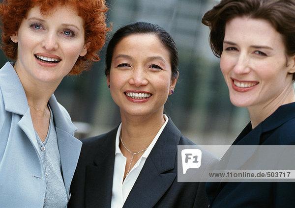 Drei Geschäftsfrauen Seite an Seite  lächelnd vor der Kamera