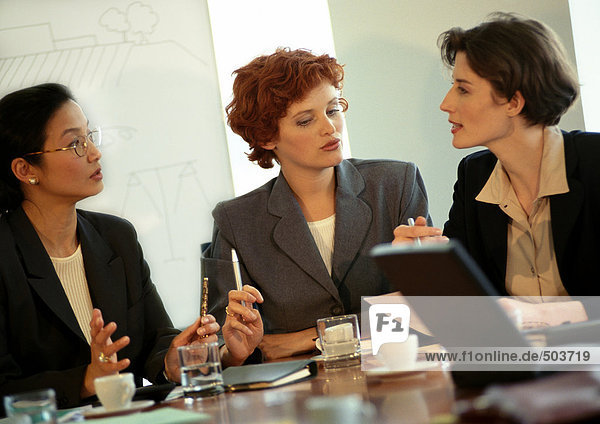 Three businesswomen sitting at conference table  talking