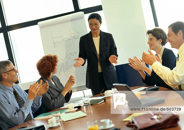 Businesswoman being applauded by colleagues in conference room