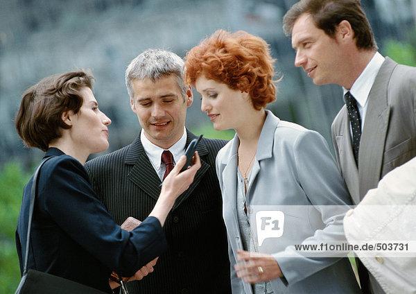 Gruppe von vier Geschäftsleuten draussen  eine hält ein Handy in der Hand
