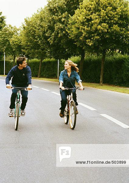 Mann und Frau fahren nebeneinander  schauen sich an  volle Länge  Vorderansicht