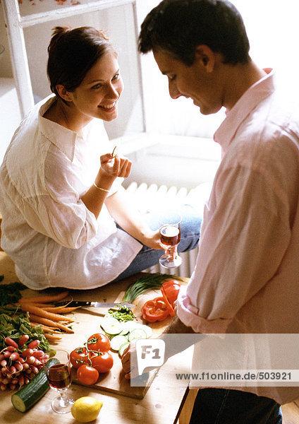 Mann hackt Gemüse auf dem Tisch  Frau sitzt auf dem Tisch  hält das Glas.