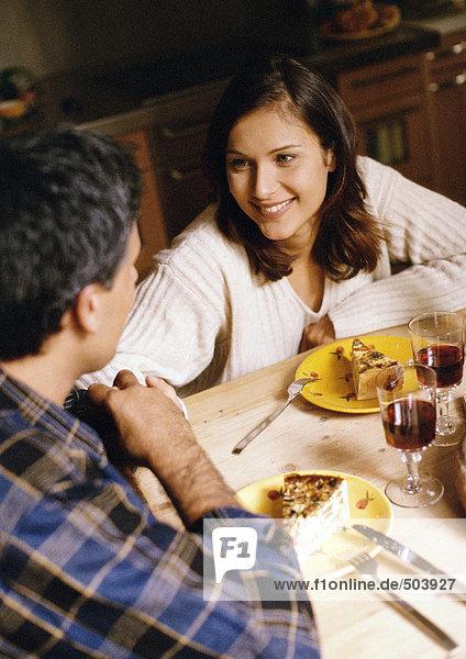 Mann und Frau bei Tisch  Fokus auf Frau im Hintergrund