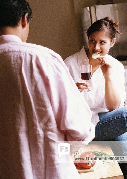 Frau isst und hält Glas  Rückansicht des Mannes im Vordergrund  verwischt