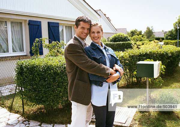 Couple standing in front of house  embracing