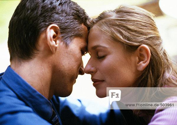 Mann und Frau  Stirn berührend  Frauenaugen geschlossen  Seitenansicht  Nahaufnahme