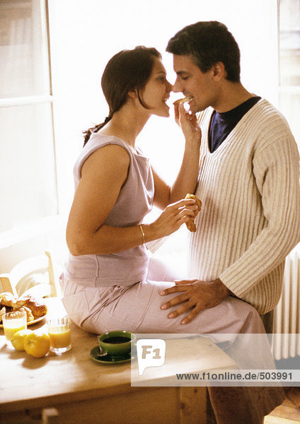 Woman sitting on table  feeding croissant to man