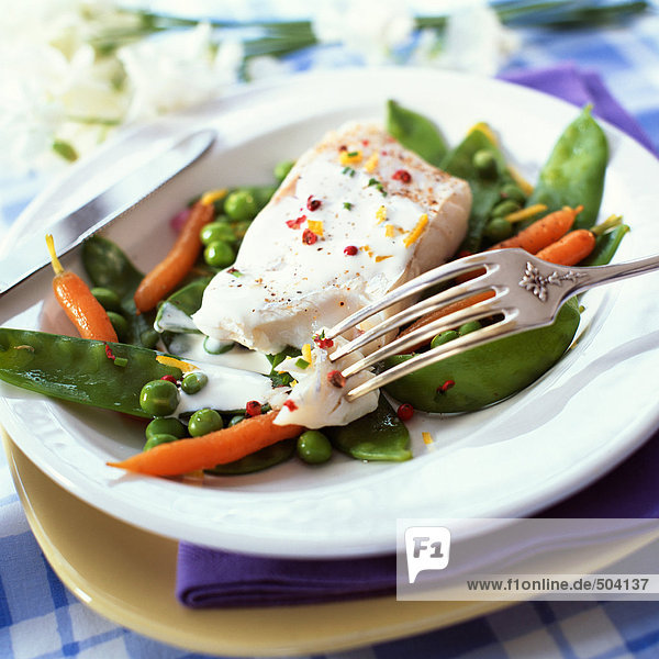 Bowl of fish and spring vegetables  close-up