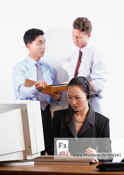 Frau schaut auf den Computer  zwei Männer im Hintergrund