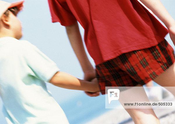 Zwei Kinder halten Hände am Strand  Rückansicht  Nahaufnahme.