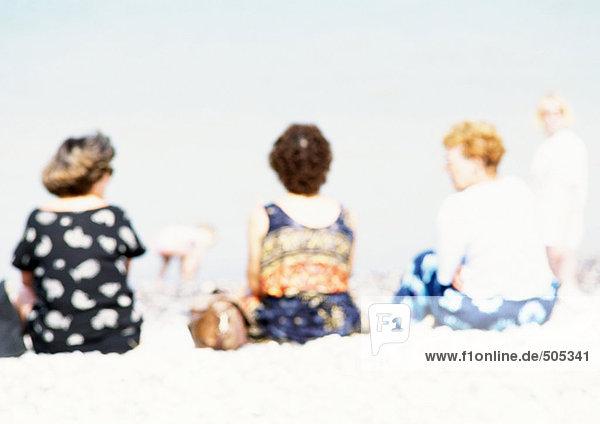 Leute  die auf Sand am Strand sitzen  Rückansicht  verschwommen