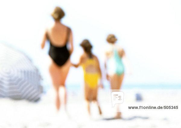 Frauen und Kinder am Strand stehend  verschwommen