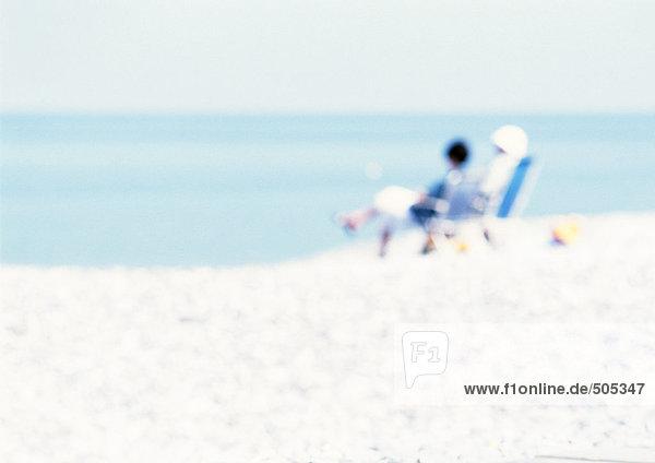 Leute  die auf Stühlen am Strand sitzen  verschwommen.