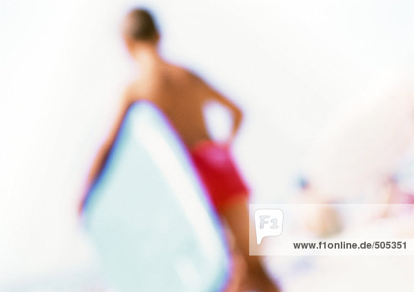 Junge hält Boogie-Board am Strand  verschwommen