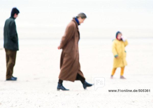 Leute in Mänteln  die am Strand spazieren gehen  verschwommen.