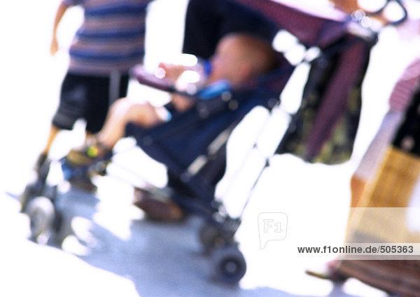Kind im Kinderwagen mit Personengruppe  verwischt