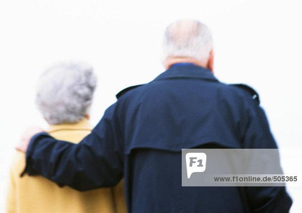 Älterer Mann und Frau  Männerarm um die Schulter der Frau  Rückansicht  verschwommen und hinterleuchtet