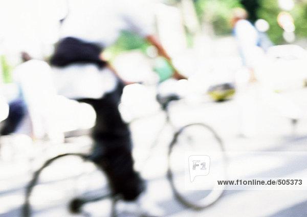 Person  die auf der Straße Fahrrad fährt  verschwommen