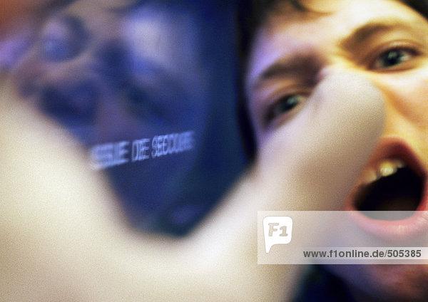Teenager-Junge schreit  Hand im Vordergrund verschwommen  Nahaufnahme