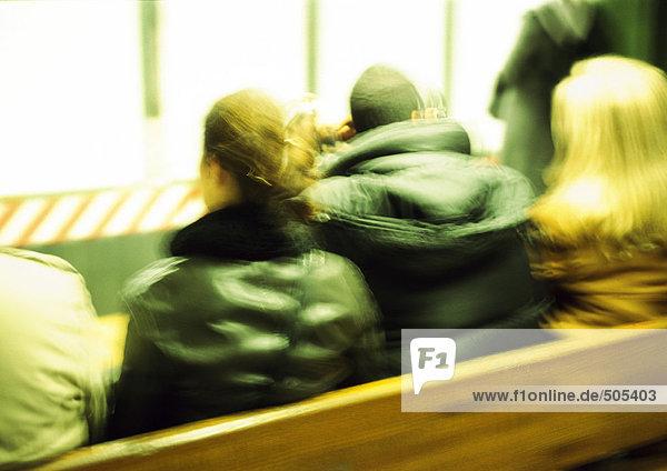Menschen in Mänteln auf der Bank sitzend  Rückansicht  Nahaufnahme