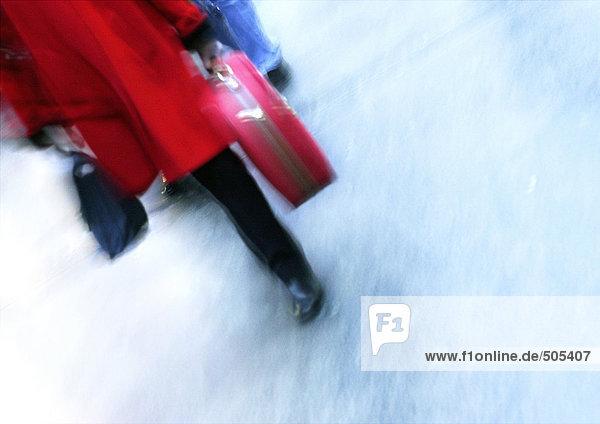 Frau geht und trägt Koffer  Unterteil  verschwommen.