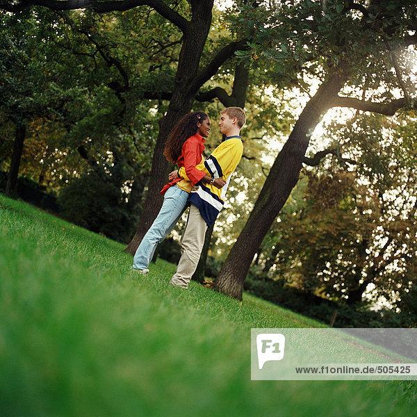 Junger Mann und Frau auf Gras stehend  umarmend  Seitenansicht  volle Länge