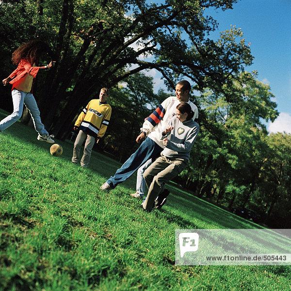 Junge Leute treten Fußball auf Rasen