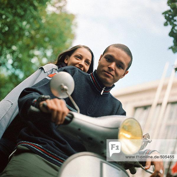 Junger Mann und junge Frau auf Motorroller  Taille hoch  Tilt