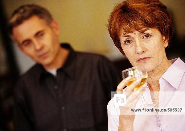 Frau hält Glas  Mann verschwommen im Hintergrund