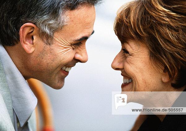 Reife Männer und Frauen sehen sich lächelnd an  Nahaufnahme.