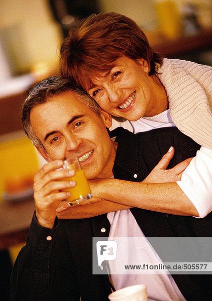 Frau umarmt Mann von hinten  Mann hält Glas Saft  Nahaufnahme  Portrait