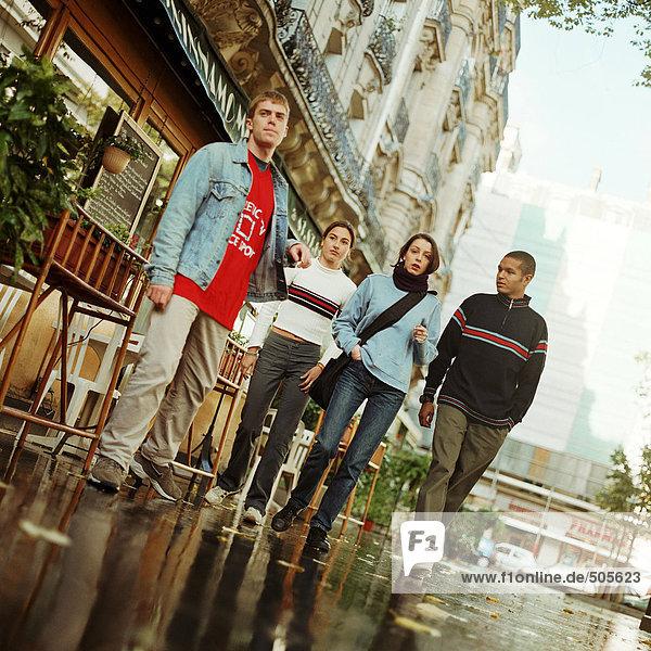 Junge Leute  die zusammen draußen in der Nähe des Cafés spazieren gehen  volle Länge