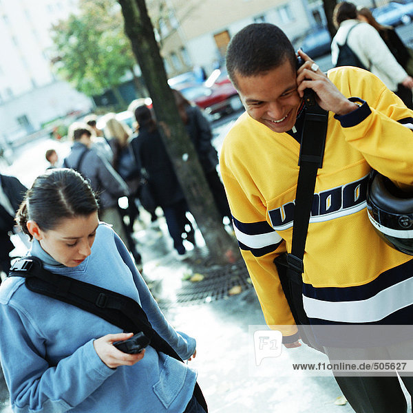 Ein junger Mann telefoniert neben einer jungen Frau  die draußen ein Handy wählt.