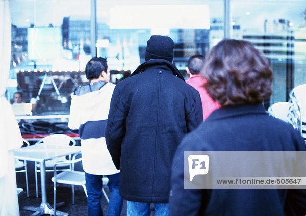 Jugendgruppe außerhalb des Cafés  Rückansicht