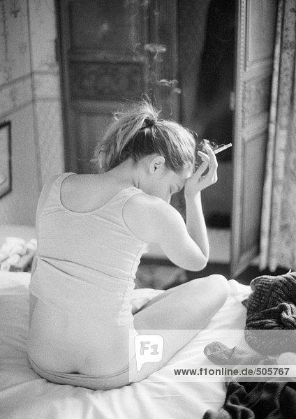 Frau auf dem Bett sitzend rauchend  Rückansicht  schwarz-weiß.