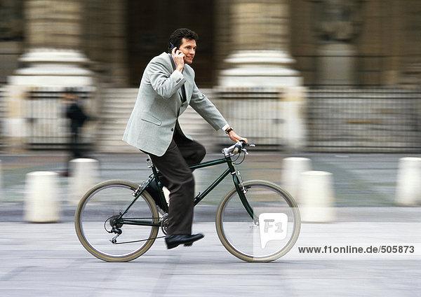 Mann im Anzug  hält Handy an Ohr und Fahrrad  verschwommen.