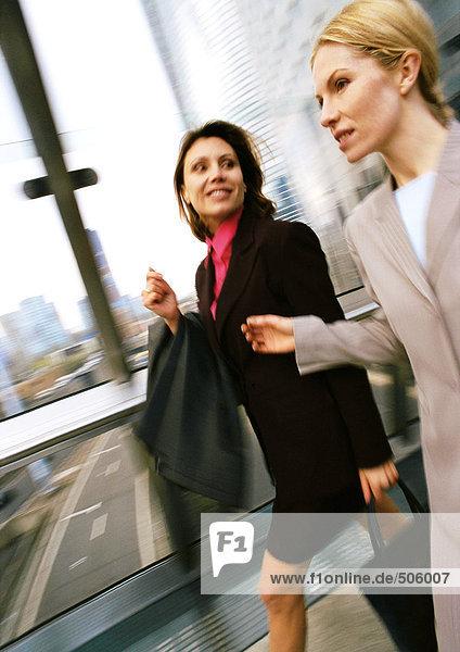 Geschäftsfrauen gehen zusammen in einem erhöhten Gang  verschwommen.