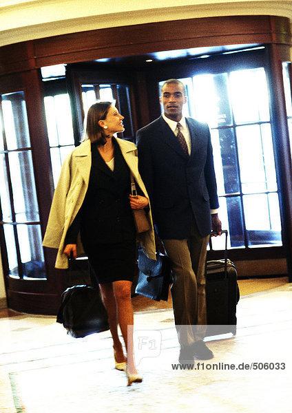 Geschäftsmann und Geschäftsfrau gehen gemeinsam im Gebäude mit Gepäck  Drehtüren im Hintergrund
