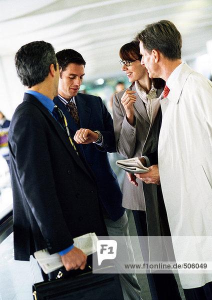 Geschäftsleute stehen zusammen  einer schaut auf die Uhr.