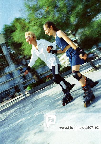 Reife Frau und Mädchen beim Inline-Skaten  verwischt