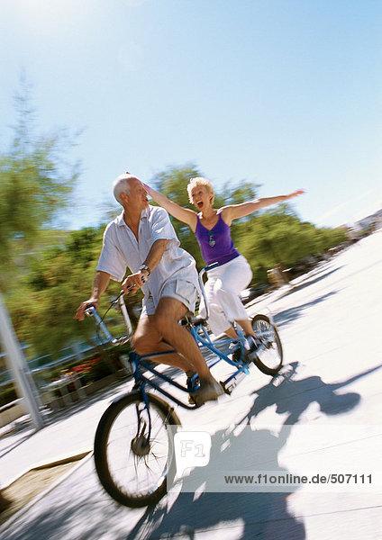 Ein reifes Paar  das zusammen auf einem Tandemrad fährt  eine Frau  die ihre Arme ausstreckt  verschwommen.