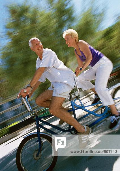 Erwachsener Mann und Frau beim gemeinsamen Tandemfahren  Seitenansicht  unscharf