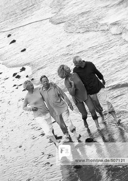 Zwei reife Paare gehen gemeinsam den Strand entlang  Blick von oben  B&W.