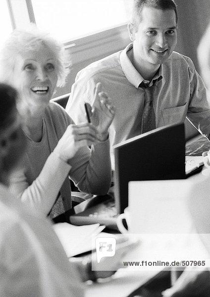 Reife Geschäftsfrau in Konferenz  lächelnd  mit anderen Geschäftsleuten  B&W