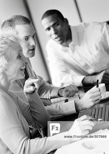 Reife Geschäftsfrau in Konferenz  lächelnd  Profil  mit zwei Geschäftsleuten  B&W